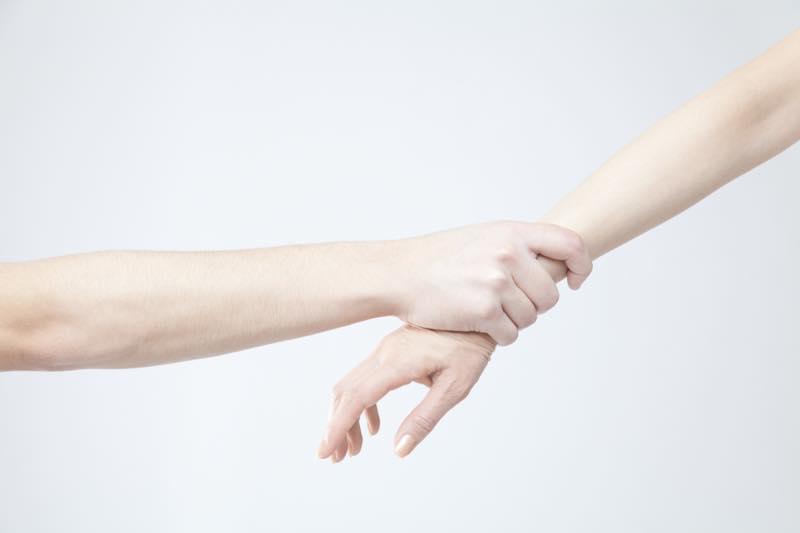 女性の手を掴む男性