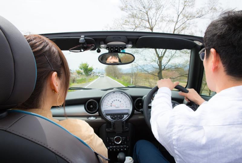 オープンカーでドライブしている男女の写真