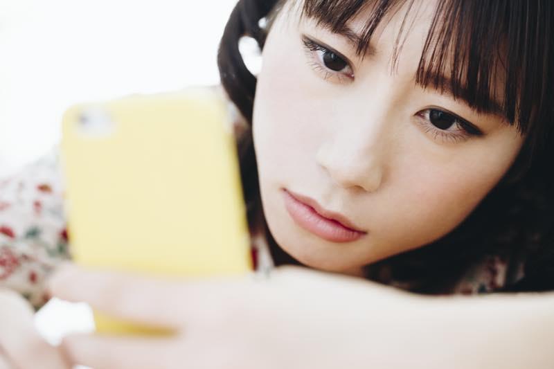 女性がスマートフォンを悲しい顔で眺めている写真