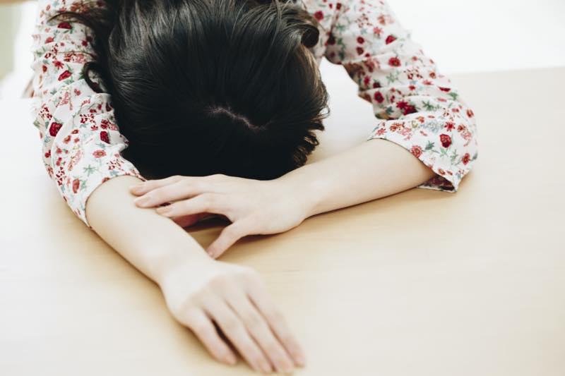 女性が机に突っ伏している写真