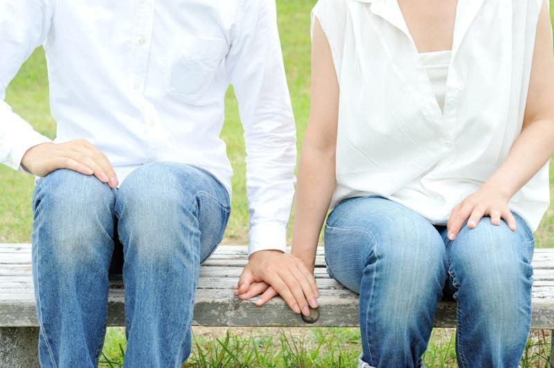 ベンチで女性の手を掴む男性