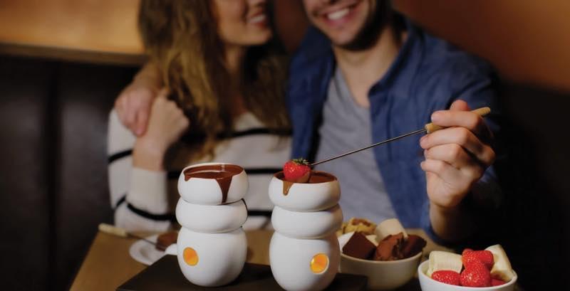 男女がチョコレートフォンデュをしている写真