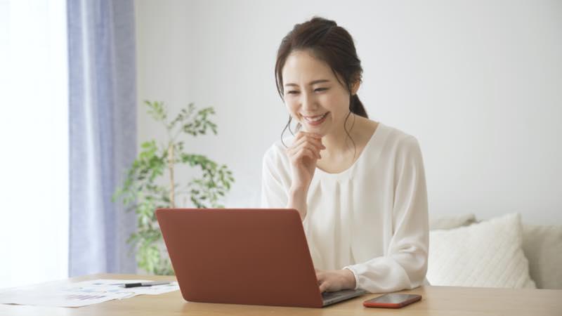 笑顔でパソコンを見る女性の写真