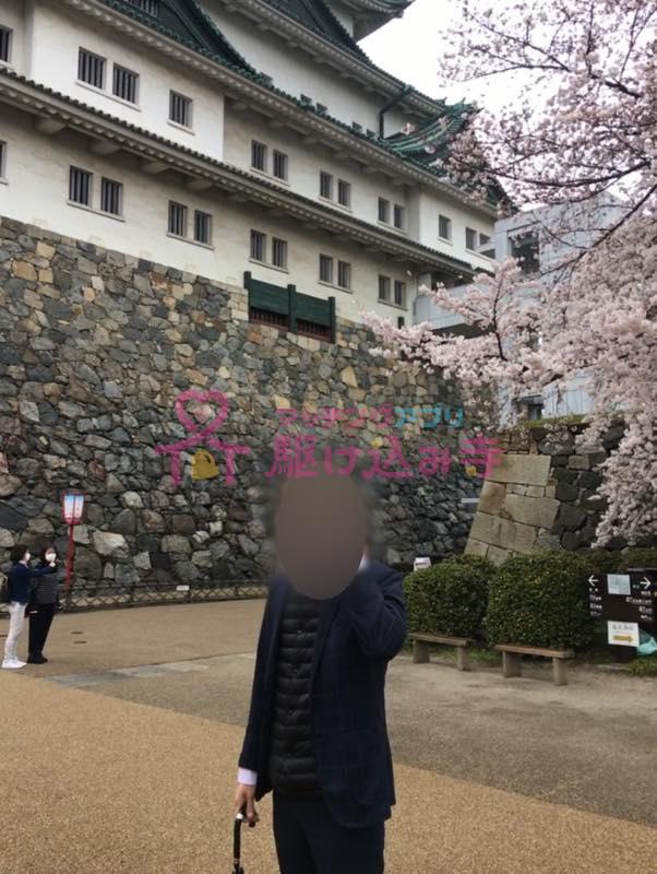 名古屋城の前で電話をする男性の写真
