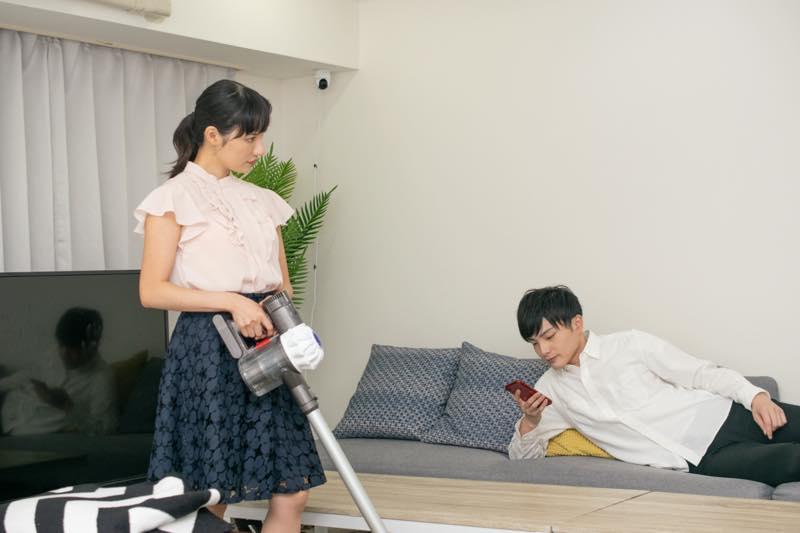 寝そべる男性の横で不満そうに掃除機をかけている女性の写真