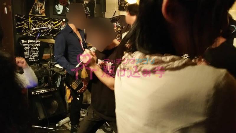 ライブハウスで熱唱している男性の写真