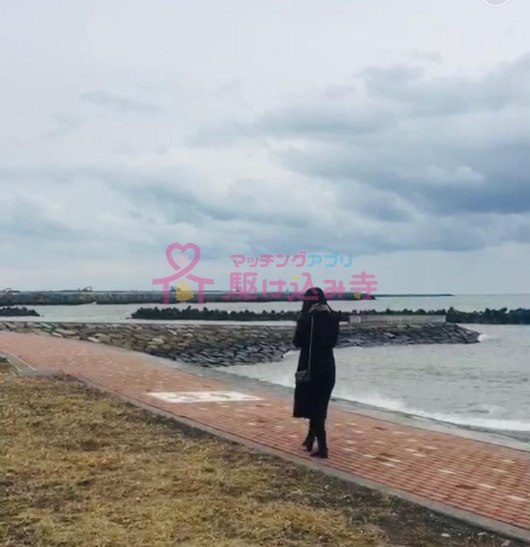 曇った海辺を歩く女性の写真