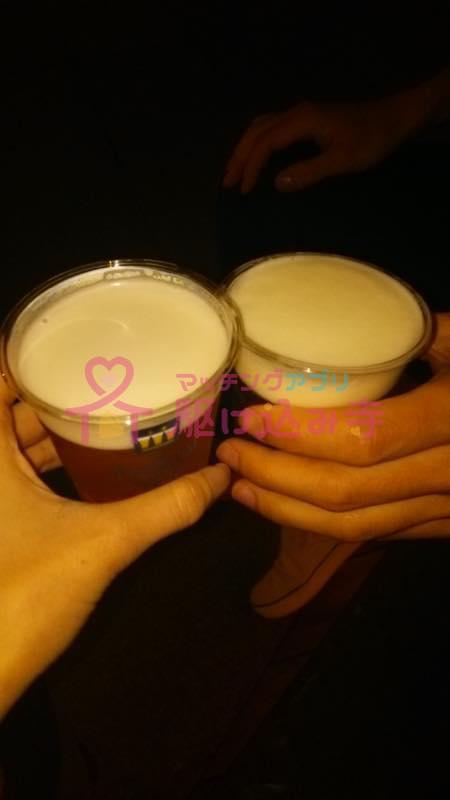 プラスチックの容器に入ったビールで乾杯するカップルの写真