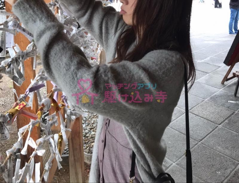 神社でおみくじを結ぶ女性の写真