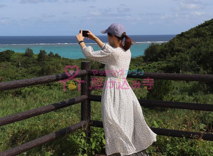 海でスマホで写真を撮る女性の写真
